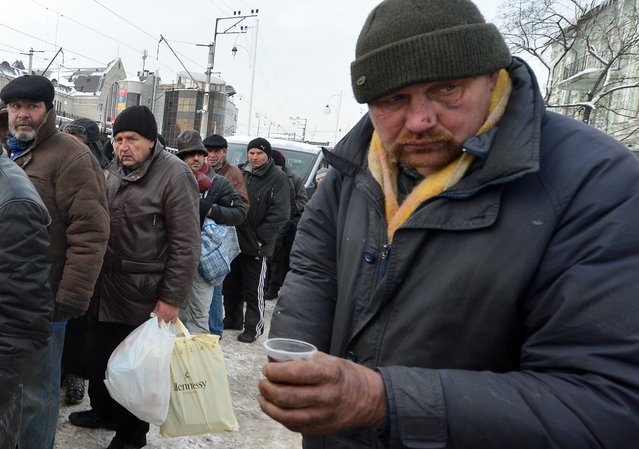Homeless people  queue to get free hot food organized by social services during frost winter day in-Kiev on December 18, 2012. Nineteen people died of exposure in Ukraine in the last 24 hours amid temperatures of minus 20 degrees Celsius (minus 4 degrees Fahrenheit), bringing the toll this month to 37, the health ministry said Tuesday. (Photo by Sergei Supinsky/AFP Photo)