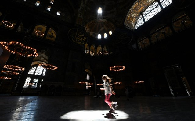 A girl wearing a protective face mask runs as the sun shines through a window on a spot inside the Hagia Sophia Museum in Istanbul on June 26, 2020. The nation of some 83 million has removed most restrictions regarding the COVID-19 pandemic, reopened restaurants and resumed mass prayers but officials have warned against complacency. (Photo by Ozan Kose/AFP Photo)