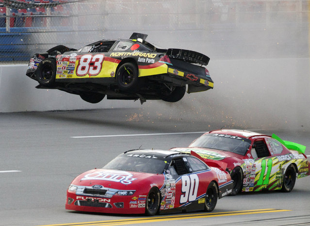 Zach Ralston (90) and Brett Hudson (11) drive past the flipping car of Mike Affarano (83) during the International Motorsports Hall of Fame 250 ARCA auto race at the Talladega Superspeedway in Talladega, Ala., May 4, 2012. (Photo by Dave Martin/AP Photo)