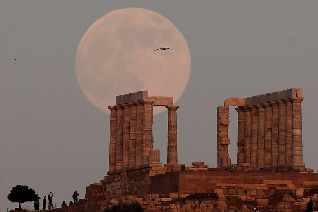 A nearly full moon rises over the Temple of Poseidon, the ancient Greek god of the seas, in Cape Sounion, east of Athens, Greece, July 8, 2017. (Photo by Costas Baltas/Reuters)