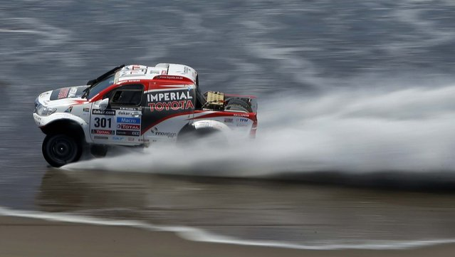 Giniel de Villiers of South Africa and Dirk Von Zitzewitz of Germany race their Toyota on a beach in the 4th stage of the 2013 Dakar Rally from Nazca to Arequipa, Peru. (Photo by Victor R. Caivano/Associated Press)