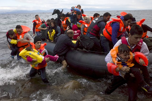 Refugees and migrants struggle to jump off an overcrowded dinghy on the Greek island of Lesbos, after crossing a part of the Aegean Sea from the Turkish coast, October 2, 2015. (Photo by Dimitris Michalakis/Reuters)