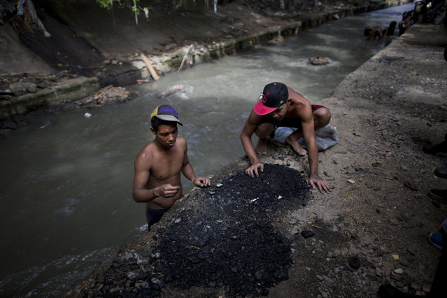 In this November 30, 2017 photo, men sort through the debris they pulled up from the bottom of the polluted Guaire River, in search of pieces of gold and anything of value to sell in Caracas, Venezuela. Venezuela sits atop the world's largest oil reserves, but the global drop in crude prices and plummeting production under nearly two decades of socialist rule has left many in the country of 30 million people struggling to survive. (Photo by Ariana Cubillos/AP Photo)