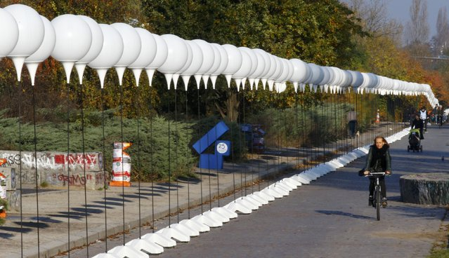 """A woman cycles along stands with balloons placed along the former Berlin Wall location at Mauerpark, which will be used in the installation """"Lichtgrenze"""" (Border of Light) in Berlin November 7, 2014. (Photo by Pawel Kopczynski/Reuters)"""