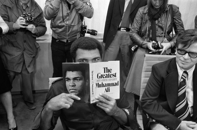 "Muhammad Ali peers over a copy of his book ""The Greatest,"" in the VIP room at the airport in Frankfurt, October 10, 1975. Ali came to Frankfurt to introduce his book at the International Book Fair. (Photo by Kurt Strumpf/AP Photo)"