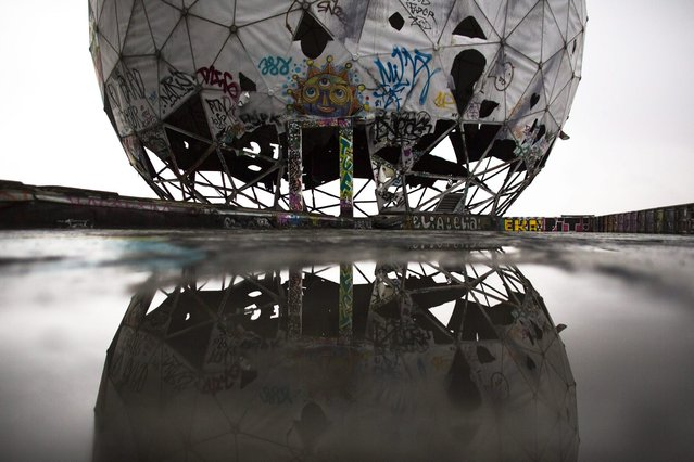 In this October 16, 2014, photo, the ruin of a vandalized golf ball shaped cover for antennas, of the abandoned former listening station of the United States National Security Agency, at the Teufelsberg (Devil's Mountain) is reflected in a puddle in Berlin. The listening station which was active until the early nineties is now used by graffiti artists and can be visits only with guided tours. (Photo by Markus Schreiber/AP Photo)