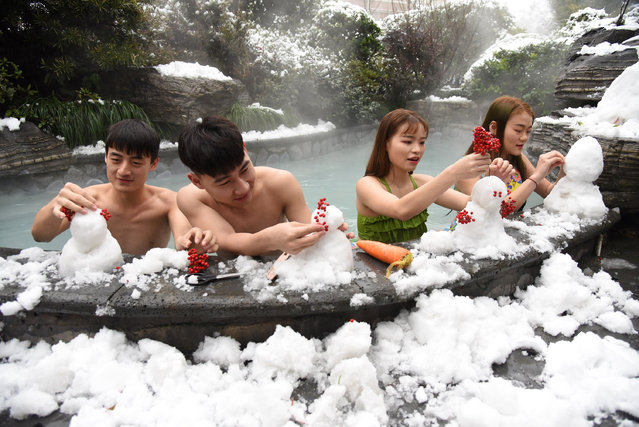 Visitors make snowmen beside a pool at a hot spring in Hangzhou, in China's eastern Zhejiang province on January 26, 2018. China's central and eastern regions have been hit by heavy snowfalls in recent days, causing disruptions to flight and train schedules. (Photo by AFP Photo/China Stringer Network)