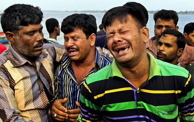 Men mourn the victims of a ferry that capsized on the banks of the Meghna River on February 8, 2013.The passenger ferry capsized after colliding with another ship on a river dumping as many as 100 people into the water. (Photo by A.M. Ahad/Associated Press)