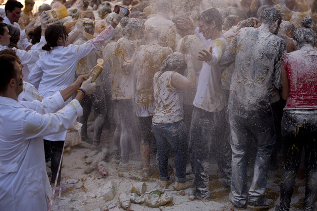 Food is poured on freshman year medical students already covered with food stuffs during the faculty of medicine hazing at the University of Granada, in Granada on October 15, 2015. (Photo by Jorge Guerrero/AFP Photo)