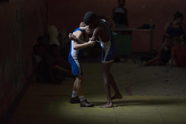 Children practice during a wrestling lesson in downtown Havana, October 23, 2014. Picture taken October 23, 2014. (Photo by Alexandre Meneghini/Reuters)