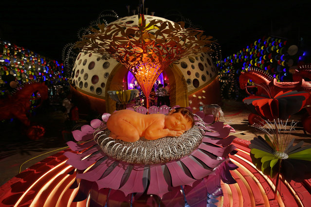 A silicon made baby girl (C) is part of an installation made with wood, fiber, metal, bamboo and colored paper, under the theme 'Save the Girl Child' by painter and sculptor Pradip Das, as part of the preparations of the Durga Puja festival in Calcutta, India, October 16, 2015. Bengalis all over the world will mark the festival representing the victory of good over evil and the celebration of female power. (Photo by Piyal Adhikary/EPA)