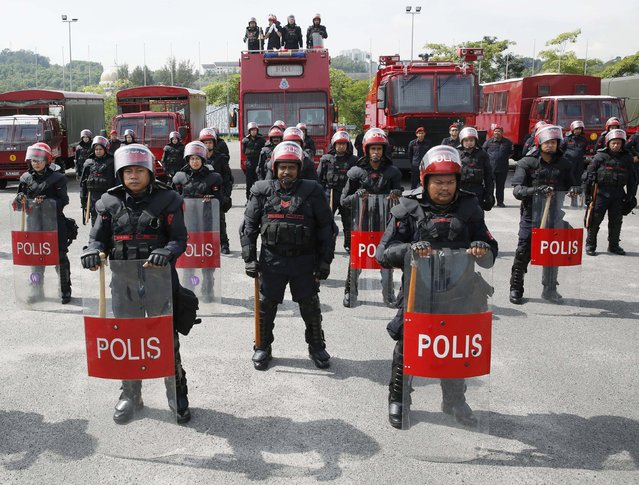 Malaysia's public order police, the Federal Reserve Unit (FRU), pose for photographs wearing riot control equipment at their headquarters in Kuala Lumpur November 20, 2014. In Malaysia, the FRU are only permitted to use firearms in cases where the protesters are using firearms. Firearms have not been used in the 59 years since the FRU was formed. (Photo by Olivia Harris/Reuters)