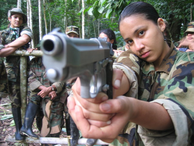 A member of the Revolutionary Armed Forces of Colombia (FARC) pose for a picture at a camp in the Colombian mountains on February 2005. (Photo by Frank Piasecki Poulsen)