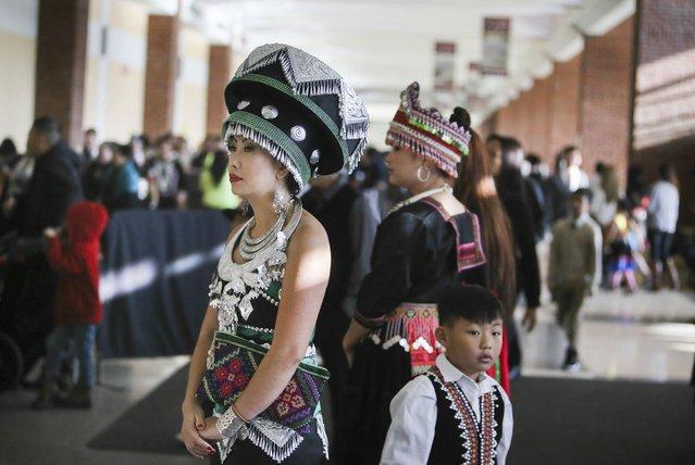 Duabhli Vang of St. Paul, left, wears Hmong Chinese adornment at the Minnesota Hmong New Year celebration Saturday, November 29, 2014, at the Saint Paul RiverCentre in St. Paul, MN. (Photo by David Joles/Star Tribune)