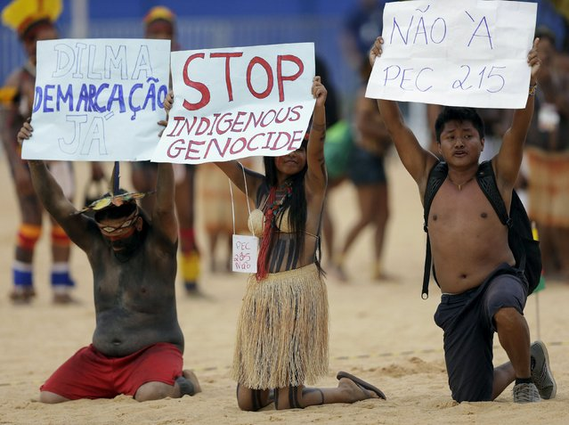 Indigenous people from several tribes protest inside the sports arena during the first World Games for Indigenous Peoples in Palmas, Brazil, October 25, 2015. (Photo by Ueslei Marcelino/Reuters)