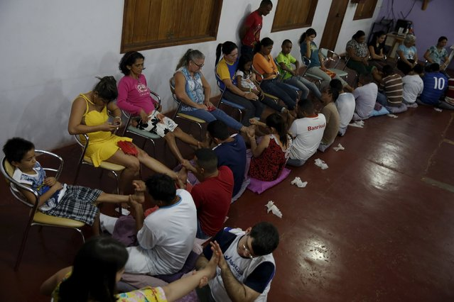 Inmates conduct Ayurvedic massage on their relatives during a half-day visit as part of the ACUDA programme, at a complex of ten prisons in Porto Velho, Rondonia State, Brazil, August 28, 2015. Ayurveda is an ancient Hindu system of holistic healing. The massage is taught to the prisoners to help them understand the human body and engender a greater sense of compassion for others, according ACUDA. (Photo by Nacho Doce/Reuters)