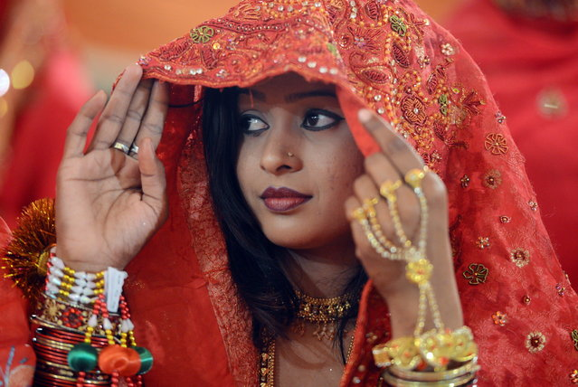 A Pakistani bride looks on during a mass marriage ceremony in Karachi late March 26, 2013.  Some 110 couples participated in the mass wedding ceremony organised by a local charity welfare trust Al Ghousia. (Photo by Asif Hassan/AFP Photo)