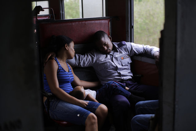 In this March 23, 2015 photo, an off-duty police officer travels with his family to Santa Clara during a long trip through the province of Holguin in Cuba. From east to the west, trains offer a fine-grained, slow-moving view of Cuba that few foreigners ever see. (Photo by Ramon Espinosa/AP Photo)