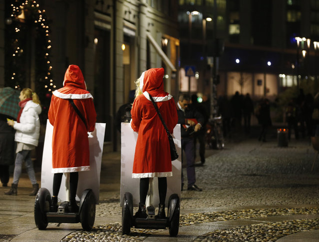 Two girls dressed with Santa Claus costumes display advertising on they Segway electric vehicles as they tour downtown Milan, Italy, Friday, December 5, 2014. (Photo by Luca Bruno/AP Photo)