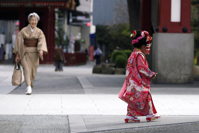 A child in colorful kimono walks at Tokyo's Asakusa district on the occasion of Shichigosan celebration Thursday, October 22, 2020. The festival celebrates children aged three, five and seven for their well-being. (Photo by Eugene Hoshiko/AP Photo)