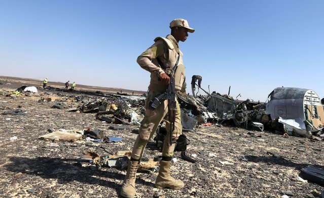 An Egyptian army soldier stands guard near debris from a Russian airliner at its crash siteat the Hassana area in Arish city, north Egypt, November 1, 2015. (Photo by Mohamed Abd El Ghany/Reuters)