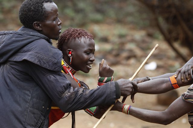 A man and women hold onto a girl as she tries to escape when she realised she is to to be married, about 80 km (50 miles) from the town of Marigat in Baringo County December 7, 2014. (Photo by Siegfried Modola/Reuters)