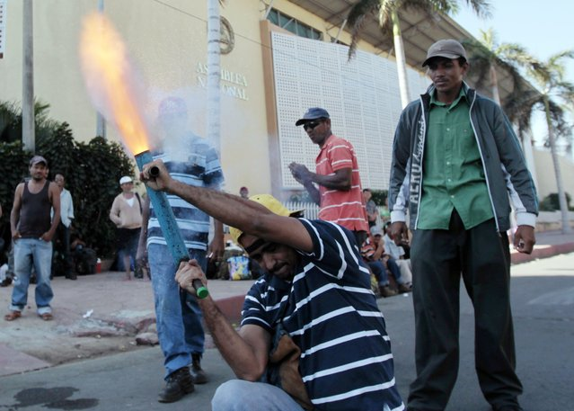A man fires a homemade mortar during a protest outside the National Assambly Building in Managua December 9, 2014. A dozen former employees of sugar cane fields urged legislators to pass a law forcing sugar mills to pay compensation for the damage to the workers' health as a result of what the protesters believe is the constant contact with pesticides and herbicides used for pest and weed control on the plantations. (Photo by Oswaldo Rivas/Reuters)