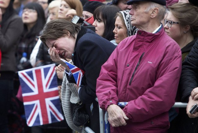A member of public weeps as the coffin of former British prime minister Margaret Thatcher is transported from St Clement Danes church towards St Paul's Cathedral during her funeral procession, in London April 17, 2013. Thatcher, who was Conservative prime minister between 1979 and 1990, died on April 8 at the age of 87. (Photo by Richard Pohle/Reuters)