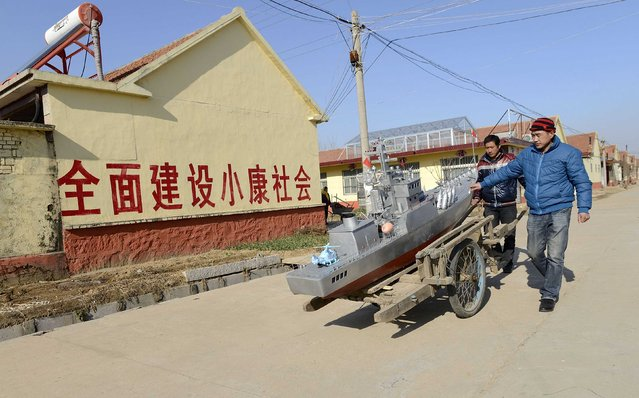 Residents push a cart to transport a homemade replica of a destroyer vessel made by retired fishboat captain Guo Changhai (not pictured), as they walk along a road after a test run in Xiaojia village of Rizhao, Shandong province, December 13, 2014. Guo, 56-year-old, who sold his fishboat in 2005 after being the captain for 27 years, started making vessel models out of recycled waste such as wooden planks, cans, steel wires and pipes. (Photo by Reuters/China Daily)