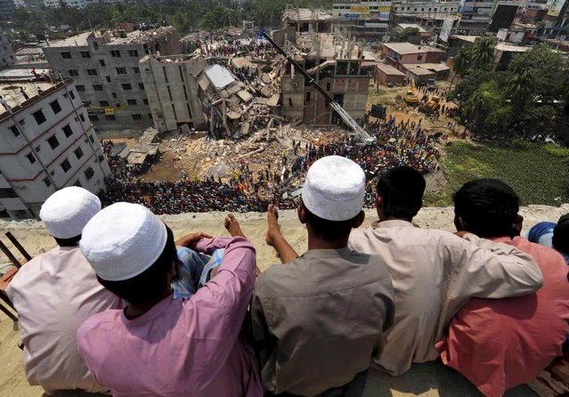 People watch as rescue workers continue their operations at the collapsed Rana Plaza building in Savar, 30 km (19 miles) outside Dhaka April 25, 2013. Survivors from the garment factory that collapsed in Bangladesh killing at least 228 people described on Thursday a deafening bang and tremors before the eight-floor building crashed down under them. (Photo by Reuters/Stringer)