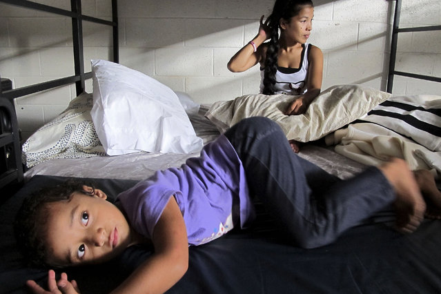 In this October 9, 2015 photo, Keioleen Helly, 3, foreground, and her aunt, Kifency Kinny, 24, lay on a bed in the Institute for Human Services family shelter in Honolulu. Kifency's mother, Kionina Kaneso, arrived in 2004 and worked odd jobs as a dishwasher and assembly line worker to pay for her son's flight to Hawaii so he could get medical treatment for a heart condition. (Photo by Cathy Bussewitz/AP Photo)