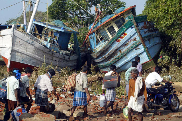 In this December 28, 2004 file photo, villagers walk with their belongings past two boats that were washed ashore by tidal waves at Nagappattinam, in the southern Indian state of Tamil Nadu. (Photo by Gautam Singh/AP Photo)