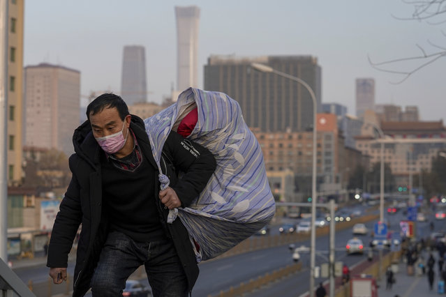 A migrant worker wearing face masks to help curb the spread of the coronavirus walks up to a pedestrian bridge in Beijing, Sunday, December 6, 2020. Provincial governments across China are placing orders for experimental, domestically made coronavirus vaccines, though health officials have yet to say how well they work or how they may reach the country's 1.4 billion people. (Photo by Andy Wong/AP Photo)