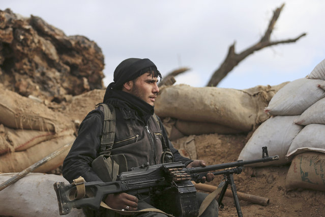 A rebel fighter from the Free Syrian Army's Al Rahman legion takes up position behind sandbags in Jobar, a suburb of Damascus, December 22, 2014. (Photo by Bassam Khabieh/Reuters)