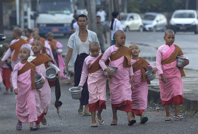 Novice Buddhist nuns walk to collect alms in Yangon, Myanmar, Monday, November 9, 2015. (Photo by Gemunu Amarasinghe/AP Photo)