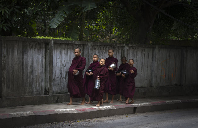 "A group of Myanmar Buddhist monks walk to collect their morning ""alms"" or offerings, Friday, June.16, 2017, in Yangon, Myanmar. (Photo by Thein Zaw/AP Photo)"