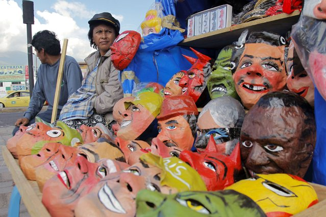 People sit next to masks on a street in Quito December 30, 2014. (Photo by Guillermo Granja/Reuters)