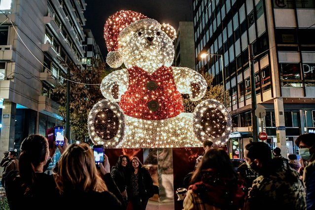 People take pictures of an illuminated giant Christmas bear in a main commercial street of Athens, on December 21, 2020, as Greece celebrates Christmas season under lockdown, with closed shops and restaurants, while the government urges people to stay home and avoid family gatherings as the Covid-19 deaths and infectionon of the remain high. (Photo by Louisa Gouliamaki/AFP Photo)