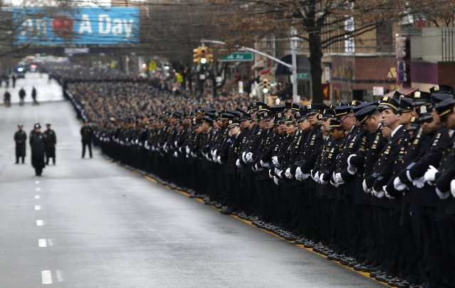 Police stand in formation down 65th street as they listen to the funeral service for New York Police Department officer Wenjian Liu in the Brooklyn borough of New York January 4, 2015. (Photo by Mike Segar/Reuters)