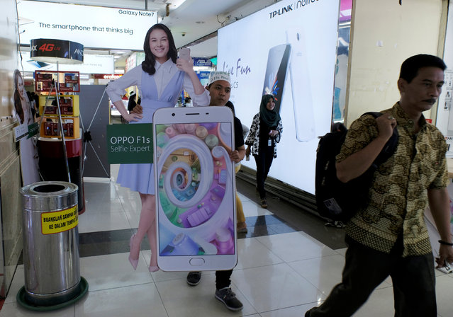 A salesperson carries an OPPO smartphone banner of Indonesia's filmstar Chelsea Islan at ITC Roxymas shopping mall in Jakarta, Indonesia, September 22, 2016. (Photo by Reuters/Beawiharta)