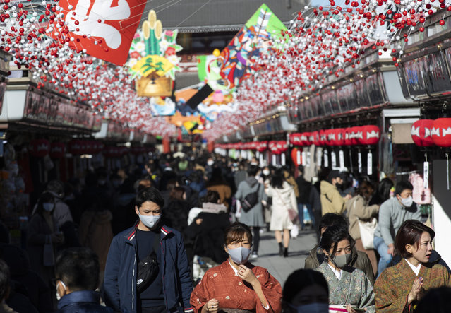 """People wearing face masks to help curb the spread of the coronavirus visit Sensoji temple on New Year's Eve in Tokyo Thursday, December 31, 2020. On the New Year's Eve, the shopping street is crowded by last minute shoppers who look for ingredients for """"osechi"""" or Japanese traditional New Year dishes. (Photo by Hiro Komae/AP Photo)"""