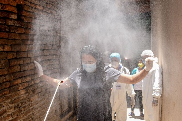 Health workers wearing protective gear spray disinfectant on a local woman (C) in an alley during a government-imposed nationwide lockdown as a preventive measure against the COVID-19 coronavirus, in Kathmandu on May 3, 2020. (Photo by Prakash Mathema/AFP Photo)