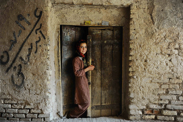 An Afghan girl stands in the doorway of her house in the old sector of Herat on June 5, 2013.  Over a third of Afghans are living in abject poverty, as those in power are more concerned about addressing their vested interests rather than the basic needs of the population, a UN report said. (Photo by Aref Karimi/AFP Photo)