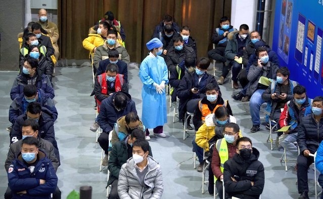 People wait on chairs after being inoculated with a Covid-19 vaccine at the Chaoyang Museum of Urban Planning in Beijing on January 15, 2021. (Photo by Noel Celis/AFP Photo)