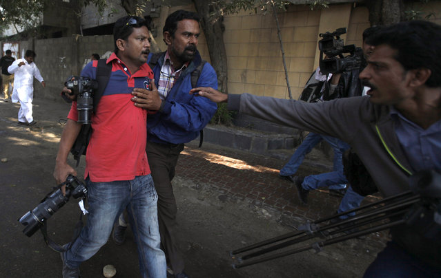 Asif Hassan (L), a photographer of French news agency Agence France-Press (AFP), shot during a protest against satirical French weekly Charlie Hebdo, is helped by a fellow photographer in Karachi January 16, 2015. (Photo by Akhtar Soomro/Reuters)