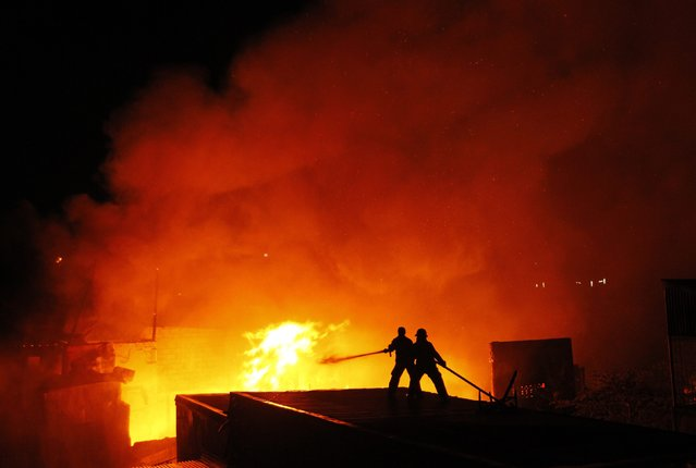 Filipino firemen try to extinguish a fire at a residential area in Manila, Philippines, 12 January 2015. More than 100 houses were razed by a fire leaving around 300 families homeless in a residential area in Manila. The cause for the fire is yet to be determined, officials said.  (Photo by Ritchie B. Tongo/EPA)