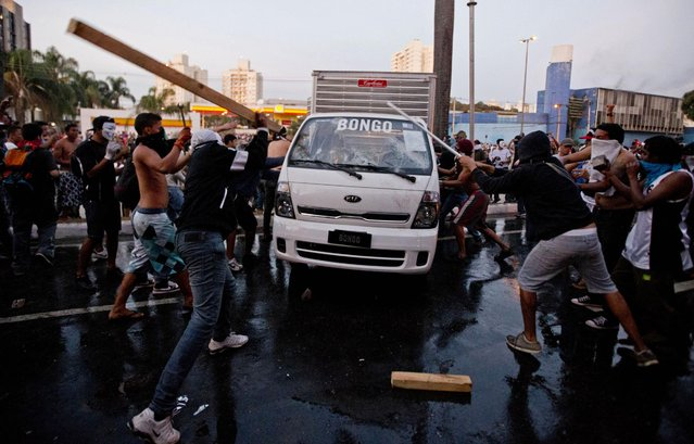 Protesters destroy a van during a demonstration in Belo Horizonte, Brazil, Wednesday, June 26, 2013.  Brazilian protesters and police clashed Wednesday near a stadium hosting a Confederations Cup soccer match, as thousands of demonstrators trying to march on the site were met by tear gas and rubber bullets. (Photo by Victor R. Caivano/AP Photo)