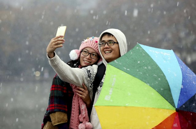 A couple takes a selfie with a mobile phone during a visit to the West Lake amid snowfall in Hangzhou, Zhejiang province, China, December 5, 2015. (Photo by Reuters/Stringer)