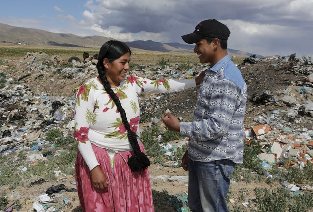 Bolivian student Esteban Quispe, 17, (R) talks with his mother Teresa near a rubbish dump in Patacamaya, south of La Paz, December 10, 2015. (Photo by David Mercado/Reuters)