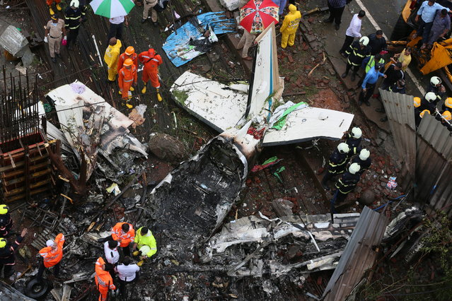Rescuers stand around the wreckage of a plane that crashed at the construction site in Mumbai, India, 28 June 2018. According to news reports, at least five people died after a chartered plane Beechcraft King Air C 90 turboprop crashed into a construction site in Ghatkopar area. (Photo by Divyakant Solanki/EPA/EFE)
